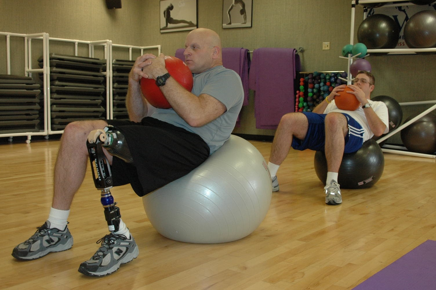 Wounded veteran with a leg prosthetic doing Pilates in a class