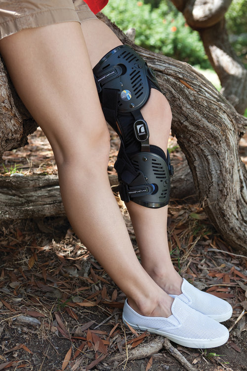 A woman wearing a knee orthosis on her left leg