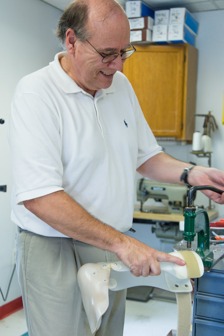 An on-site technician working on a prosthetic inside of our Fairfax facility