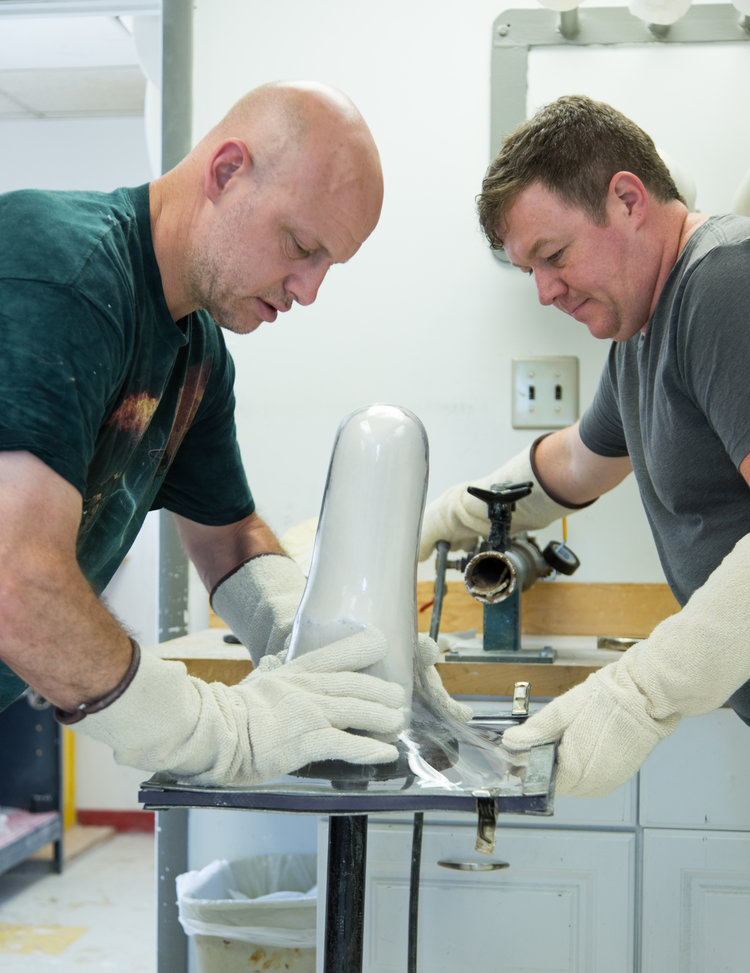 Two MCOP Fairfax technicians working on a prosthetic inside the Fairfax clinic